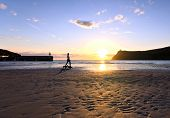 stock photo of dog-walker  - Woman walking dogs on a Beach during sunset in Port Erin on the Isle of Man - JPG