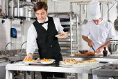 Young waiter placing dishes in tray with chef working in commercial kitchen