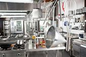 picture of saucepan  - Variety of utensils hanging in commercial kitchen - JPG