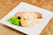 Grilled salmon steak with sauce of cheese and caviar, greens, lemon and olive
