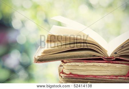 Close up on old book on colorful bokeh background poster