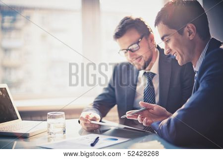 Image of two young businessmen using touchpad at meeting poster