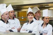 Team of chefs looking away with one smiling at camera standing in a kitchen with crossed arms
