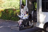 stock photo of compassion  - A woman in a wheelchair is helped off a van using a chair lift - JPG