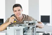 stock photo of hardware  - Handsome cheerful computer engineer repairing open computer in bright office - JPG