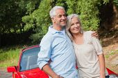 Happy mature couple posing by their red convertible on bright day