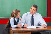 Mature male teacher looking at schoolgirl against chalkboard in classroom
