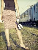 Vintage photo of young woman with shoes in her hand on the railway
