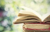 stock photo of piles  - Close up on old book on colorful bokeh background - JPG