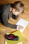 boy writing on paper, lying on the ground