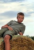 13 years old boy on a  Bale of Hay in Field in Summer