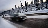 Motion Blur of Car Driving Down Snow Covered Road