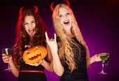 Photo of two young females with Halloween pumpkin and cocktails with scorpions having fun