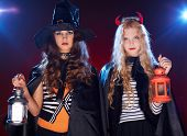 Portrait of two Halloween girls with lanterns looking at camera