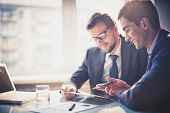 stock photo of meeting  - Image of two young businessmen using touchpad at meeting - JPG