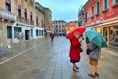 VENICE - NOVEMBER 13: Two elderly women on the street under umbrellas on a rainy day and discuss the
