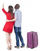 young traveling couple with suitcas pointing at wal. Back view. Rear view people collection. backsid