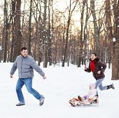 stock photo of sled  - Young happy family in winter park - JPG