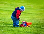 Boy plays with a toy car on the green lawn.