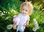 Little blond girl with dandelions.