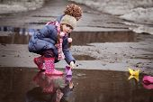 girl playing in puddles