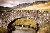 Ancient stone bridge over river,Highlands, Scotland, UK. Retro style processing.