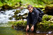 Happy teenager washing his hands in a mountain river