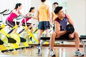 Chinese Asian group of men and woman doing sport exercise or training in fitness gym with barbell an