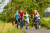 Family with three girls having a weekend excursion on their bikes or bicycles on a summer day in bea