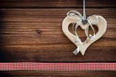 clipped wooden heart hanging on sun burned wood