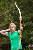 Concentrating blonde woman practicing archery in the countryside