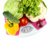 Fresh vegetables on scales on grey background