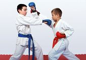 stock photo of karate  - With a red and a blue belt athletes doing paired exercises  karate - JPG