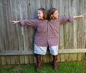 twin girls fancy dressed up pretending be siamese with his father shirt pointing finger