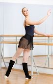Wearing leotard and warmers female ballet dancer dances near barre and mirrors in studio