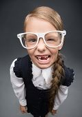 Wide angle portrait of little girl in glasses without front teeth, on grey background. Concept of le