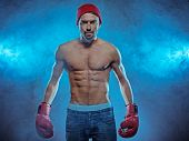 Young athletic boxer exhibiting his six-pack abdominals wearing gloves, blue jeans and a beanie hat in a smoky background