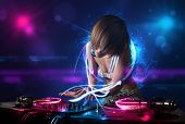 stock photo of disc jockey  - Beautiful disc jockey playing music with electro light effects and lights - JPG