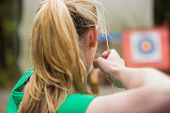 stock photo of bow arrow  - Rear view of blonde about to shoot arrow in the archery range - JPG