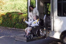 foto of lifting-off  - A woman in a wheelchair is helped off a van using a chair lift - JPG