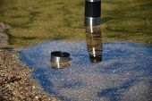 foto of thermos  - Stainless steel thermos cooling in a lake - JPG