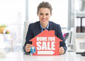 Realtor Woman Showing Keys And Home For Sale Sign