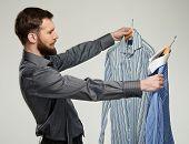 Handsome man with beard choosing shirt