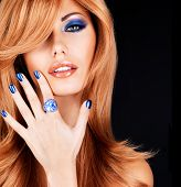 portrait of a beautiful woman with blue nails, blue makeup and  long red hairs  on black background