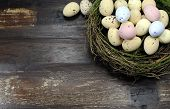 Happy Easter Candy Easter Eggs In Birds Nest On Dark Vintage Recycled Wood Background With Copy Spac