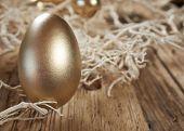 golden easter eggs in nest on vintage rustic wooden background