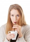 Beautiful woman is drinking from a cup with a straw. Isolated on white.