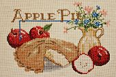 Finished cross stitch design of apple pie still life (worked on homespun aida cloth)