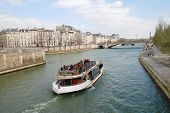 PARIS, FRANCE - MARCH 18, 2014: An excursion boat heads towards the Pont De La Tournelle on the Rive