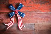 stock photo of bowing  - Indepedence Day 4th July emblem with a blue stars bow and curly red and white ribbon to celebrate the Declaration of Independence of the Untited States of America - JPG